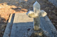 Cross and ledger of a grave. Old stone cross of a grave with a grave ledger Royalty Free Stock Images