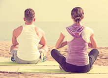 Cross-legged couple practice yoga on beach in morning Royalty Free Stock Image