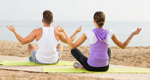 Cross-legged couple practice yoga on beach in morning Stock Images