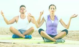 Cross-legged couple practice yoga on beach in morning Royalty Free Stock Photo