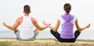 Cross-legged couple practice yoga on beach in morning Stock Photos