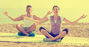Cross-legged couple practice yoga on beach in morning Royalty Free Stock Photography