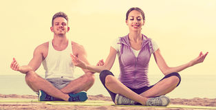 Cross-legged couple practice yoga on beach in morning Stock Photography