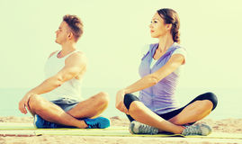 Cross-legged couple practice yoga on beach in morning Royalty Free Stock Images