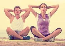 Cross-legged couple practice yoga on beach in morning Stock Photos