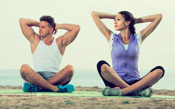 Cross-legged couple practice yoga on beach in morning Royalty Free Stock Image