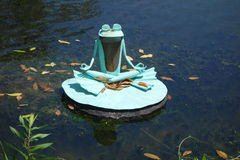 Cross-legged frog statue meditating on lily pad. This Zen frog has found peace with meditation on its lily pad in the ponds of Airlie Gardens, Wilmington, North Stock Images