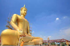 Cross-legged mediation of sitting Buddha statue. Cross-legged mediation of gold sitting Buddha statue with wooden scaffold against blue sky at wat Bang Chak in Royalty Free Stock Image