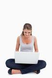 Cross-legged woman using a laptop Royalty Free Stock Image