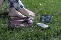 Cross legged women barefoot her shoes and tablet Stock Images