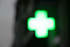 Cross of light of a pharmacy, blurred Stock Image
