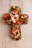 Cross made of artificial flowers and autumn plants. Royalty Free Stock Images