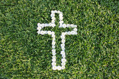 Cross made from daisy flowers. With green grass background Royalty Free Stock Photography
