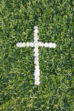 Cross made from daisy flowers. With green grass background Stock Photo