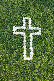 Cross made from daisy flowers. With green grass background Stock Photography