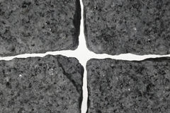 Cross made of granite. Between four granite stones from a light cross is formed royalty free stock image