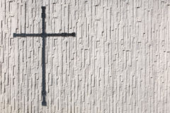 Cross made of metal on a coarse white wall Royalty Free Stock Photos
