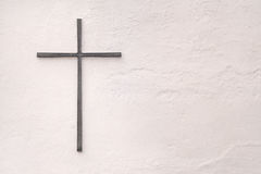 Cross made of metal on a white wall Royalty Free Stock Photography