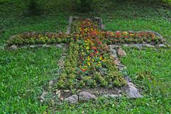 Cross made out of flowers and rocks in etno park.  Royalty Free Stock Photography