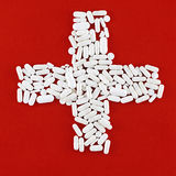 Cross made of white pills (red background) Stock Photo