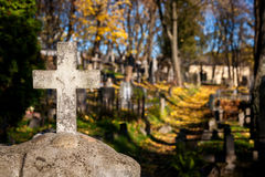 A cross monument in a cemetery Stock Images