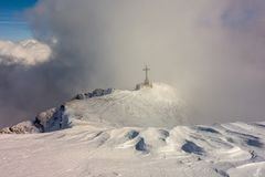 Cross monument on a mountain ridge surrounded by clouds royalty free stock photography
