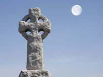 Cross and Moon. Celtic cross in a cementary with a full moon in the blue sky Stock Photos