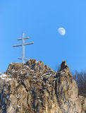 Cross and Moon. A cross on the top of the rock and a moon in background Royalty Free Stock Photos