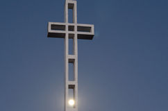 Cross with moon shining through Stock Photo