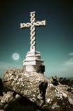 Cross in moonlight. White stone cross in the evening under the full moon light stock photo