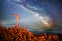 Cross on Mount Strymba. Wooden raised to the glory of God, Jesus Christ. Night light lighting a fire on a background of mountains alpine vegetation stones under royalty free stock image
