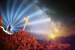 Cross on Mount Strymba. Wooden raised to the glory of God, Jesus Christ. Night light lighting a fire on a background of mountains alpine vegetation stones under royalty free stock photography
