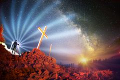 Cross on Mount Strymba. Wooden raised to the glory of God, Jesus Christ. Night light lighting a fire on a background of mountains alpine vegetation stones under royalty free stock photo