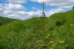 The cross on the mountain. The grass is green and the path leading to the cross Stock Photography