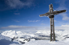 Cross on a Mountain Summit. Cross on a snow covered mountain summit in winter with blue sky and copy space Stock Images
