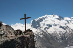 Cross in the mountains. A wooden cross stands against the blue sky with the Monta Rosa Group in the backgroud Stock Photo
