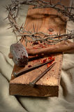 Cross With Nails, Crown of Thorns and Hammer. Cross with crown of thorns, nails and hammer over old cloth Stock Images