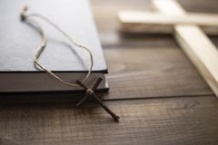 Cross near the closed Holy Bible. A wooden Christian cross with canvas thread next to the closed Bible on the table. The way to God through prayer stock images