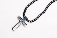 Cross Necklace. A necklace with a pendant of the holy cross made in oxidized silver, on a white fabric Stock Images