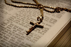 Cross Necklace and Bible. Gold crucifix necklace on open bible. Text is King James version. Selective focus on crucifix, edges of image have been very lightly royalty free stock photo