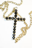 Cross Necklace. Black cross necklace with a golden chain Royalty Free Stock Photos