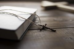Cross next the closed Holy Bible. A wooden Christian cross with canvas thread next to the closed Bible on the table. The way to God through prayer royalty free stock photography