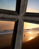 Cross On Ocean Sunset. Cross close up on peaceful ocean background of beautiful sunset or sunrise Royalty Free Stock Image