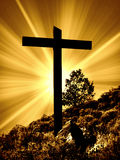 Cross. An old rugged cross on hill in Colorado with a bright light with rays shinning behind it in the background stock photos