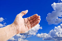 The Cross in open palm, on background sky. Stock Image