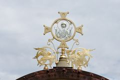 Cross on Orthodox church with Mother Mary and two angels. On cloudy sky background Stock Image