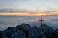 Cross over the clouds. Photo of a cross in the summit of a mountain over the clouds, at sunset Royalty Free Stock Images