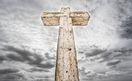 Cross over cloudy sky, wide angle. Antique stone cross covered with green lichen against cloudy sky Royalty Free Stock Images