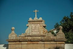 Cross over wall decorated in baroque style at Marvao. Cross over decorated in baroque style wall with the city coat of arms carved in stone, on sunny day at stock photography