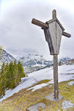 Cross overlooking the ski village of Lech. A wooden cross overlooking the Lech ski resort, part of the Arlberg Lech-Zurs ski area, from the road climbing to stock photography